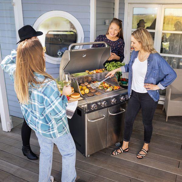 4 tjejer grillar hamburgare och grillspett på Bluegaz Z1 Gasolgrill på terrass