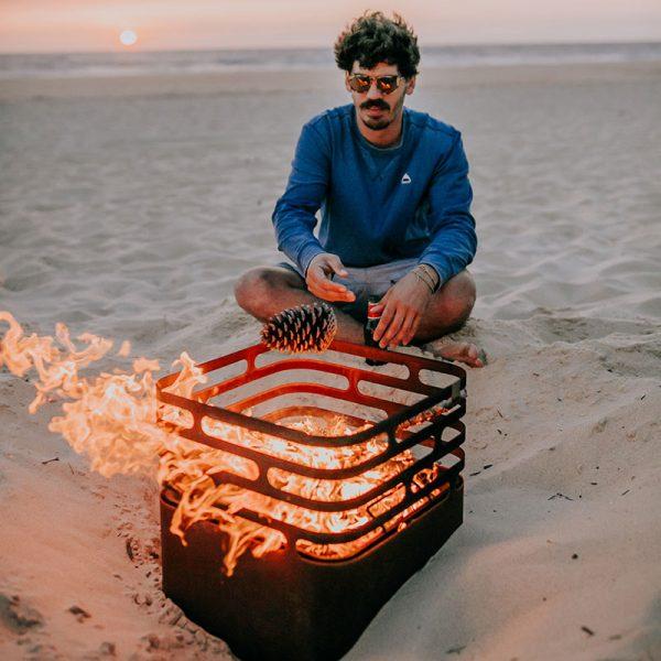 Man njuter av värmen från Höfats Cube Eldkorg & Kolgrill rost på stranden