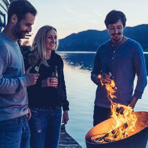 3 kompisar njuter av eld från Höfats Cone Kolgrill