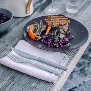 Höfats Grillbestick på tygservett bredvid tallrik med mat