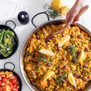 Hand serverar paella Valenciana från Vaello Paellapanna polerad 46 cm