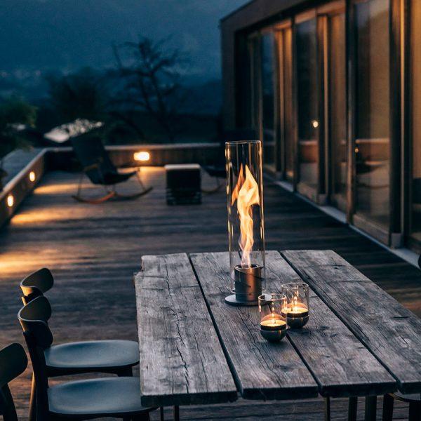 Höfats SPIN Eldlykta 120 grå brinner vackert på bord utomhus
