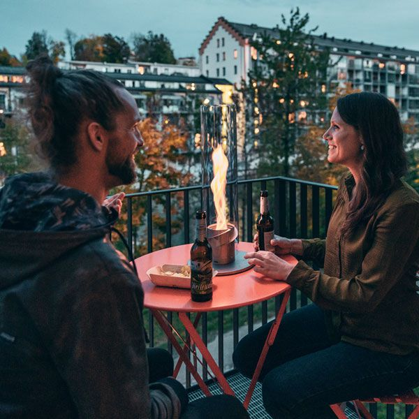 Par njuter av Höfats SPIN Eldlykta 120 grå på balkongbord