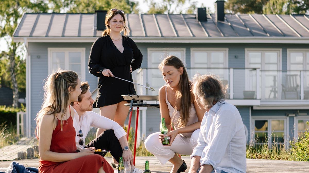 Vänner grillar paella på ett paellaset på terrass med hus i bakgrunden