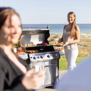 Kvinna håller tallrik med grillad mat bredvid Bluegaz X1 Premium Classic Gasolgrill med havet i bakgrund