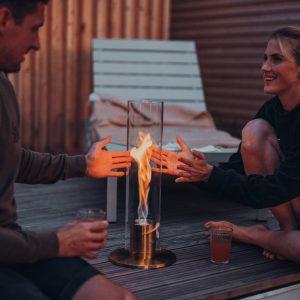 Par värmer sina händer på Höfats Spin Eldlykta 120 guld