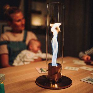 Höfats Spin Eldlykta 90 guld brinner på bord med mamma och bebis i bakgrunden