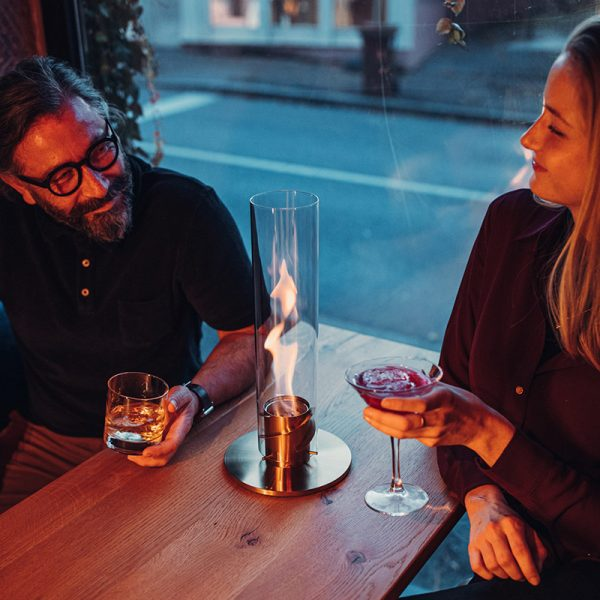 Par sitter och pratar vid bord där Höfats Spin Eldlykta 90 guld står och brinner