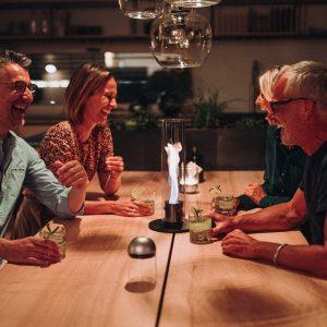 Höfats Spin Eldlykta 90 svart står på matbord och brinner med sällskap runtomkring som skrattar