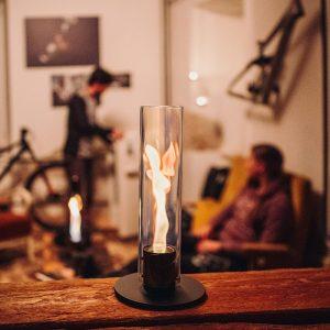 Höfats Spin Eldlykta 90 svart står och brinner på träbord i vardagsrum
