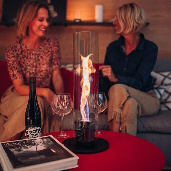 Höfats Spin Eldlykta 120 svart brinner på rött soffbord och två kvinnor sitter och pratar i soffa framför
