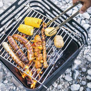 Grillar korv, majs, potatis och grillspett på Höfats Cube Eldkorg & Kolgrill svart