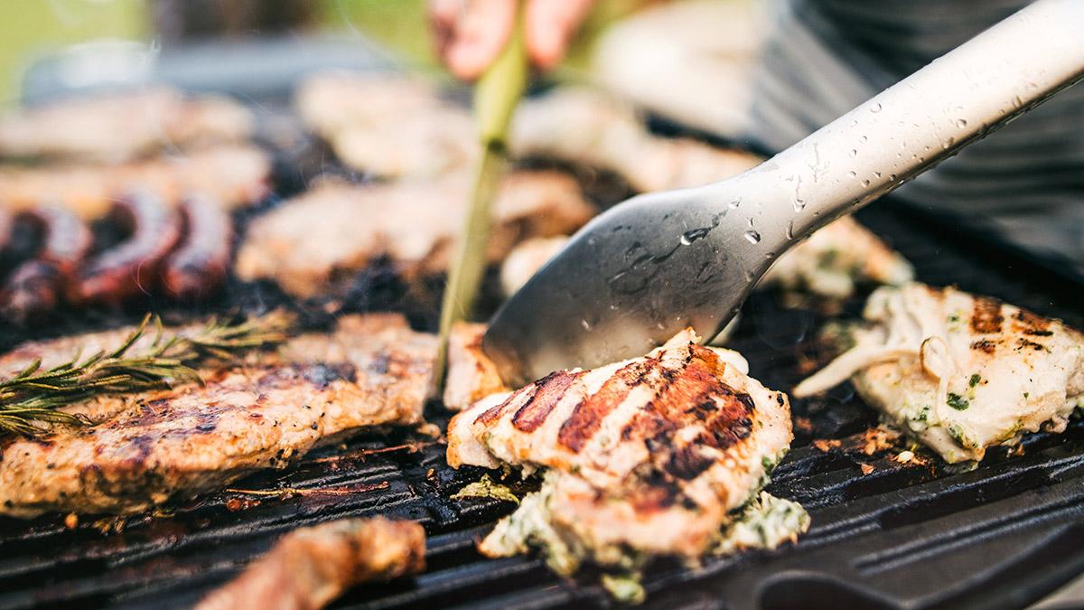 Man grillar kött och korv