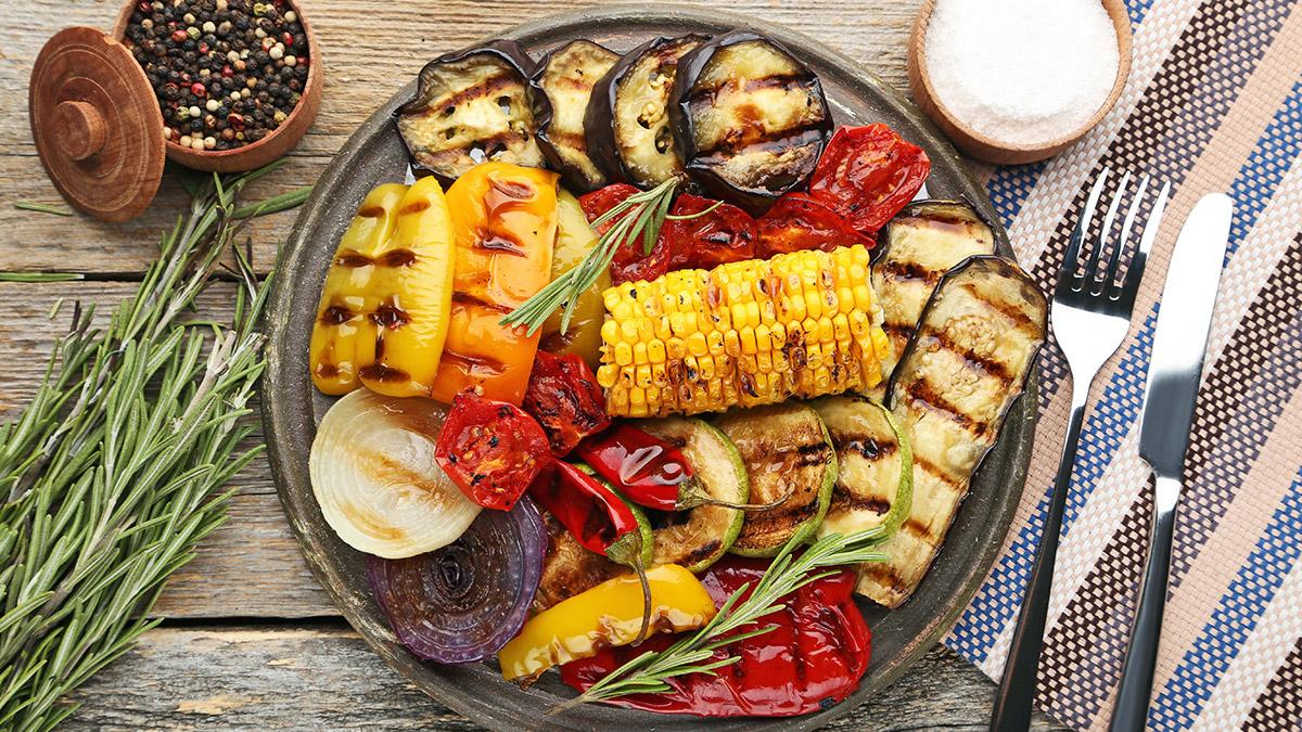 Vegetarisk grillad måltid med majs, paprika, tomater, zucchini, chili och lök