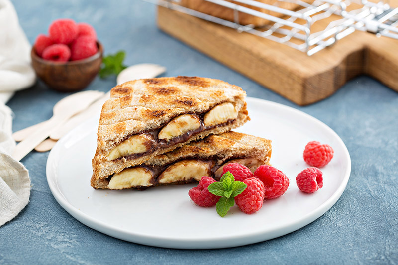 Grillad toast med choklad och banan med hallon på vit tallrik