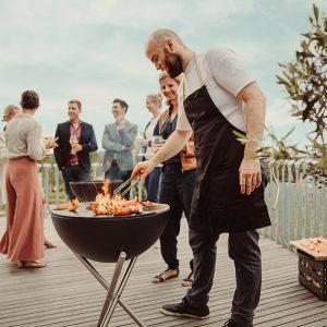 Man grillar melon på Höfats Eldskål & Kolgrill under fest