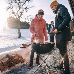 Par grillar burgare på Höfats Bowl Eldskål & Kolgrill mot vinterbakgrund