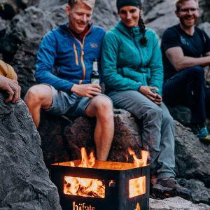 Par eldar utomhus mot bergsvägg med Höfats Beer Box eldkorg som ger lågor ifrån sig