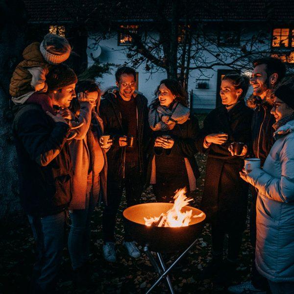 Sällskap värmer sig runt Höfats Bowl Eldskål med varsin kopp i handen