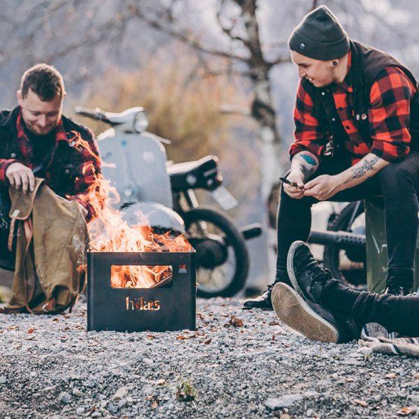 Två killar sitter utomhus med Höfats Beer Box eldkorg i dagsljus