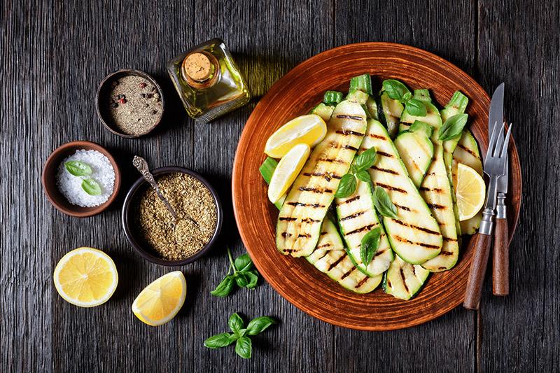 Grillad zucchini på brun tallrik med olika marinader och kryddblandningar i skålar bredvid