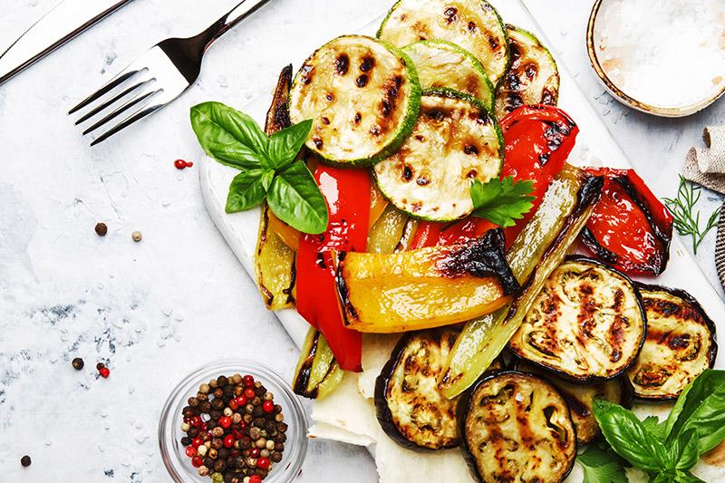 Grillad zucchini med aubergine och paprika på vit tallrik