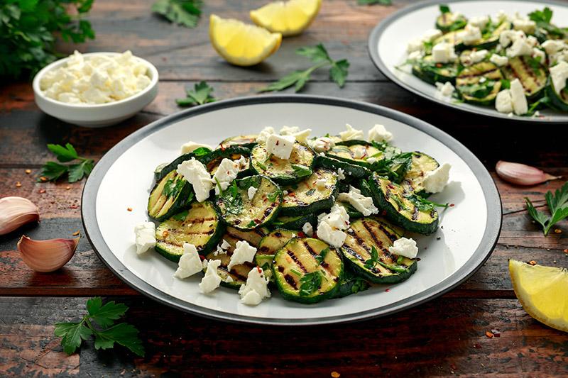 Grillad zucchini med fetaost på vit tallrik