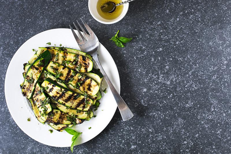 Grillad zucchini på vit tallrik