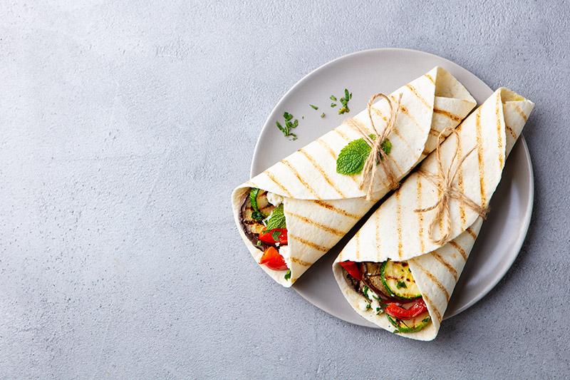 2 wraps med grillade grönsaker lindade med knut på grå tallrik
