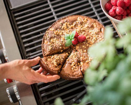 Hand tar en bit grillad kladdkaka med mjölkchoklad och jordnötter ovanpå grill