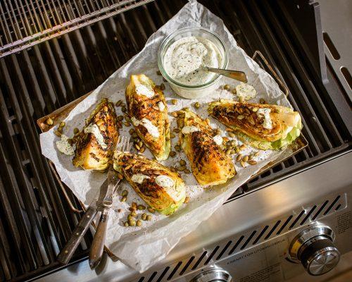 Grillad spetskål med örtmajonnäs, kapris och rostade pumpakärnor serveras på plåt ovanpå Bluegaz X1 Premium gasolgrill