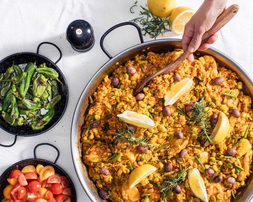 Hand håller i träslev för att servera Paella Valenciana med kyckling direkt från paellapannan
