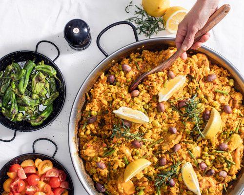 Paella valenciana på bord med vit duk och hand som tar mat