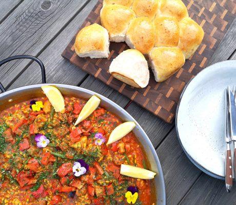 Paella med kyckling och chorizo på bord med brytbart bröd bredvis