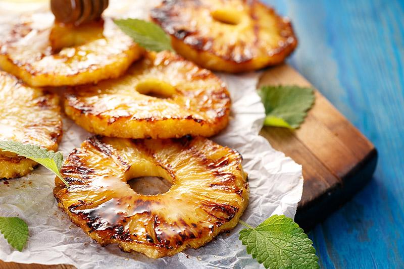 Grillad ananas med drisslad honung på bakpapper på träskärbräda