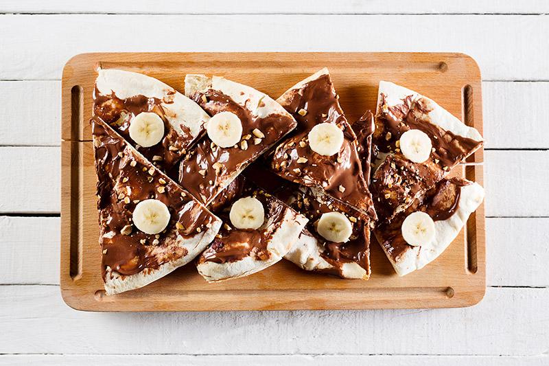 Grillade nutellapizza-slices med skivad banan och krossade hasselnötter ovanpå träskärbräda