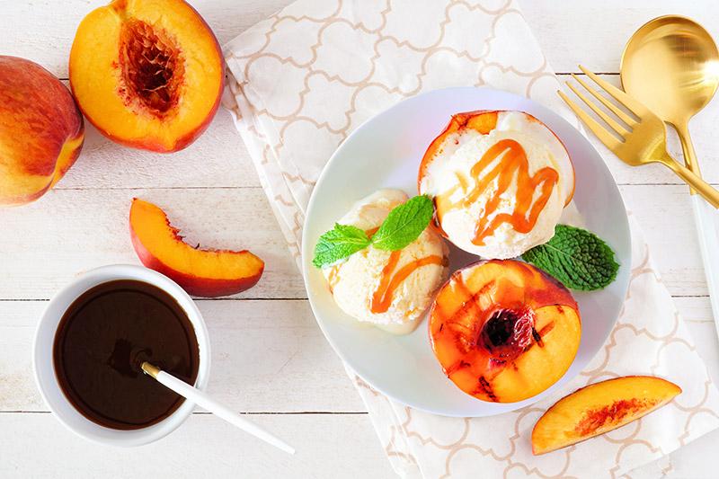 Grillad persika med vaniljglass och karamellsås på liten vit tallrik ovanpå duk