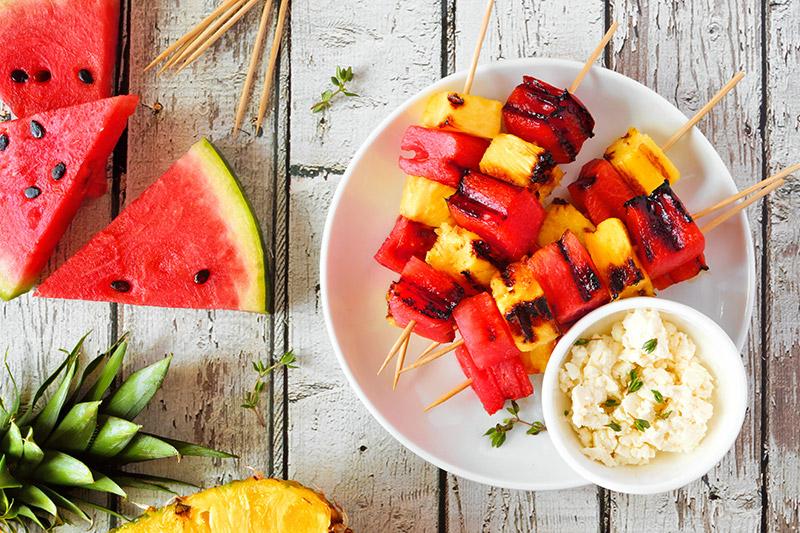 Grillade fruktspett bestående av ananas och vattenmelon på vit tallrik med skål med fetaost bredvid
