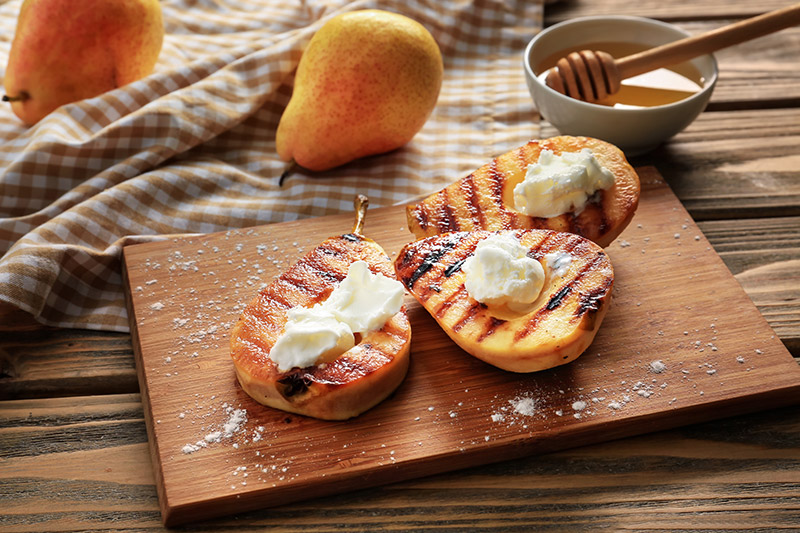 Grillade päronhalvor med en skopa vaniljglass i på träskärbräda