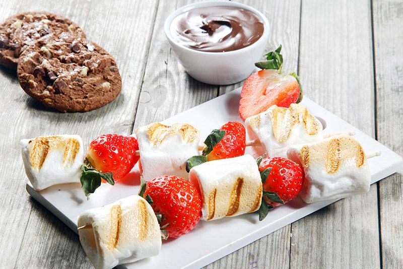 Grillade jordgubbsspett med marshmallows på en vit bricka samt med två kakor och en skål chokladsås bredvid