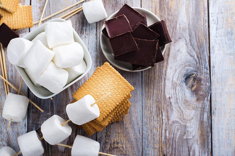 Grillade smores-ingredienser i form av marshmallows-grillspett, kex och choklad ovanpå träbord