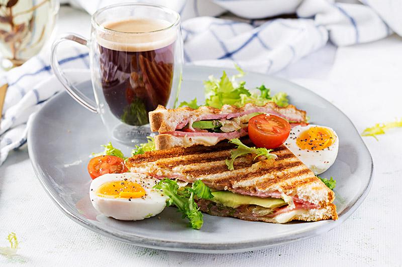 Grillad avokadotoast på grå tallrik med två kokta ägghalvor och en kopp kaffe