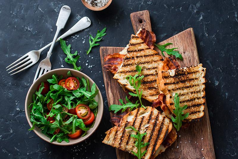 Grillad BLT-macka med mozzarella, ruccola och tomat på skärbräda