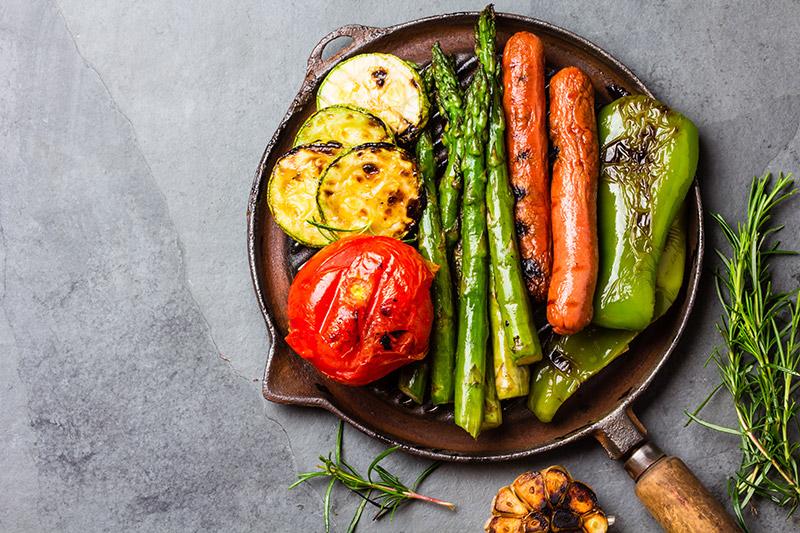Grillad korv och sparris, paprikor, zucchini och tomat på grillpanna