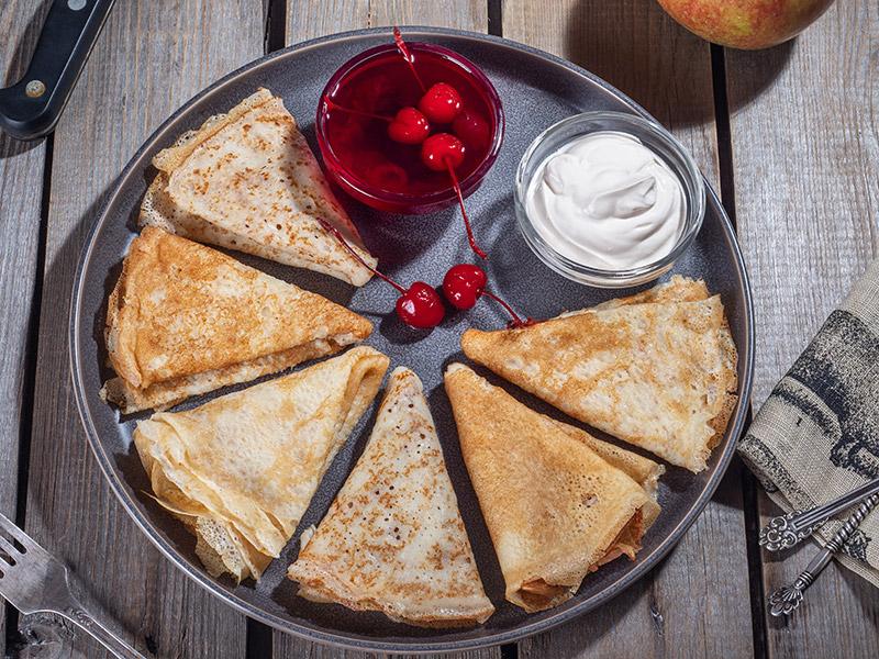 Grillade pannkakor på plancha med sylt och vispad grädde i två skålar bredvid