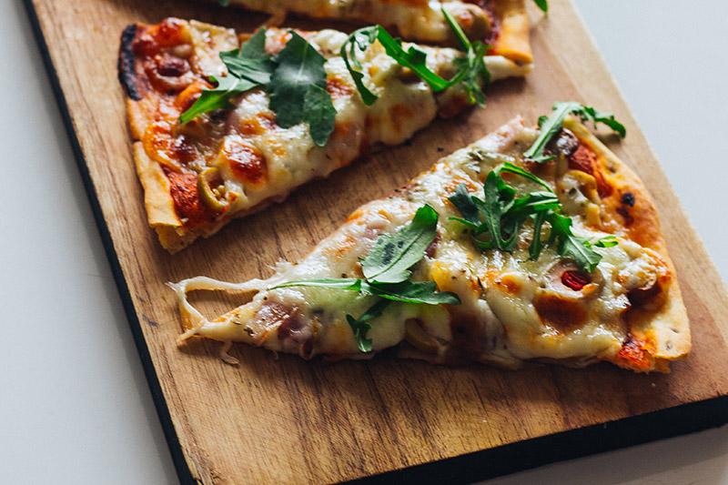 Grillad pizza med lufftorkad skinka, ost och ruccola på en skärbräda i trä