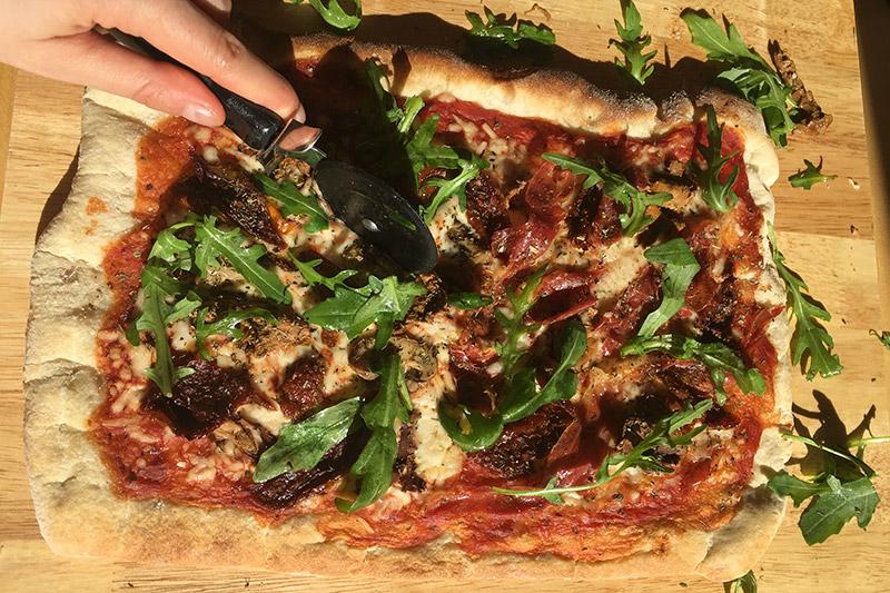 Grillad pizza på skärbärda i trä som är hälften vegan pizza och hälften pizza med lufftorkad skinka