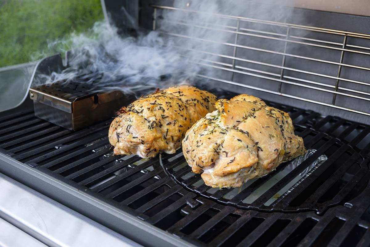 Två hela kycklingar röks på en gasolgrill med en röklåda bredvid sig på gallret