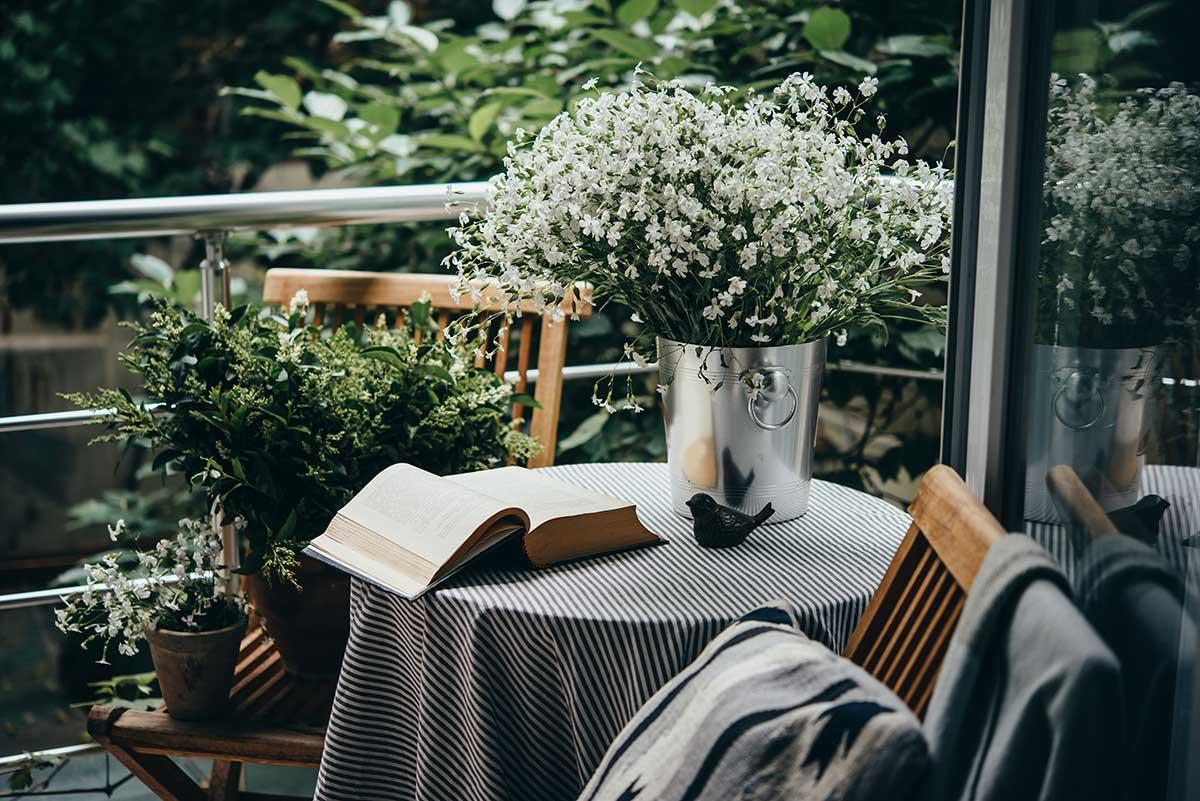 Terass med bord och stolar och en stor bukett vita blommor på bordet