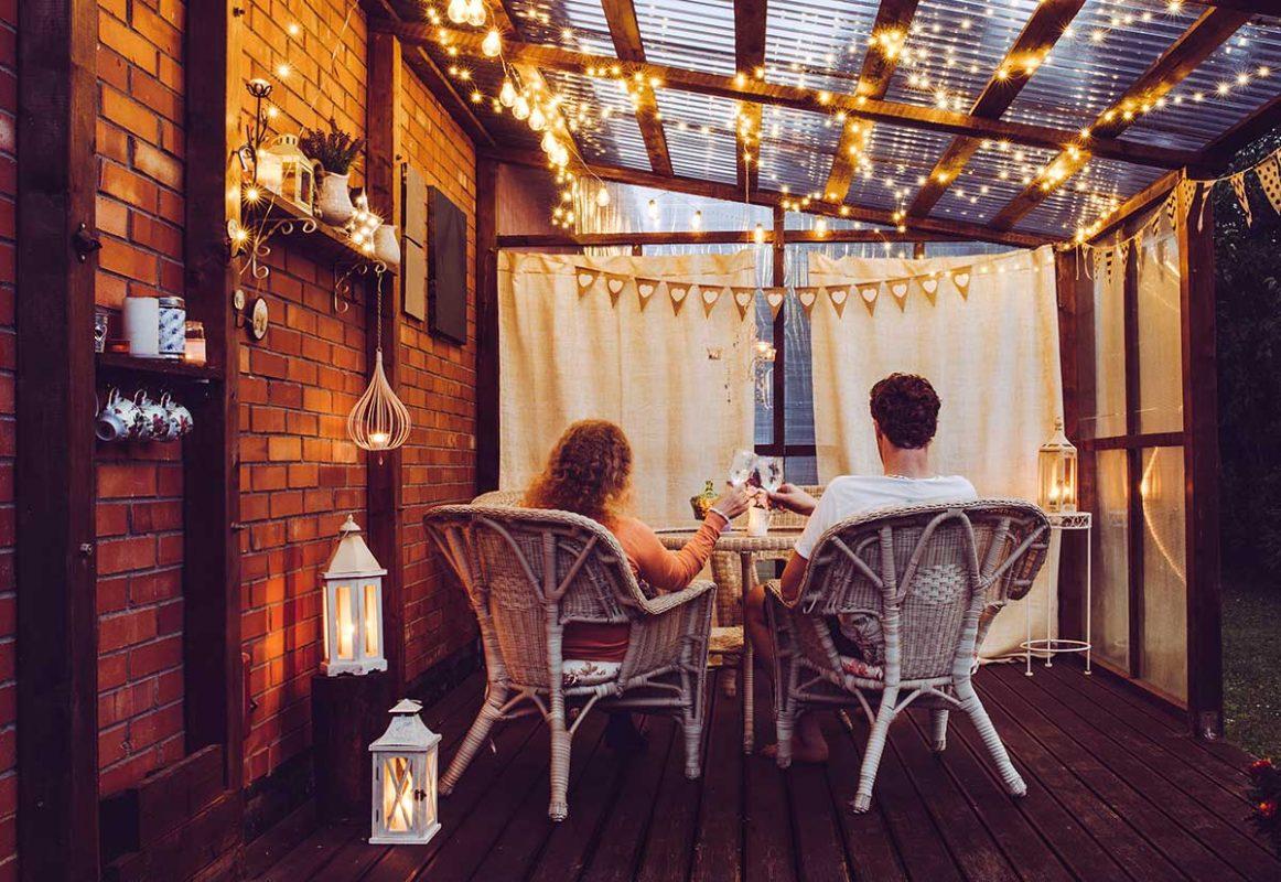 Par sitter på terassen med ljusslingor ovanför sigmot ett vitt skynke och har en mysig stund med